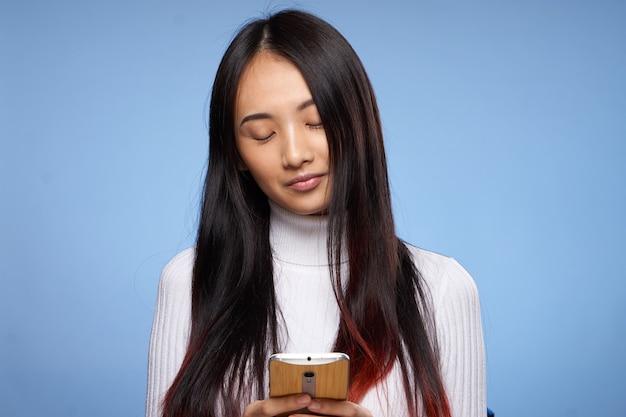 Hübsche brünette mit telefon in der hand kommunikation internet-technologie blauen hintergrund