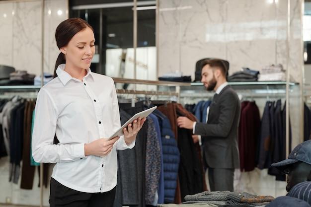 Hübsche brünette verkäuferin, die tablet-anzeige beim scrollen durch online-artikel auf hintergrund des käufers betrachtet