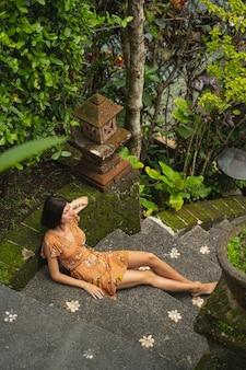 Hübsche brünette weibliche person, die exotische naturgeräusche genießt, während sie ihren urlaub auf bali verbringt