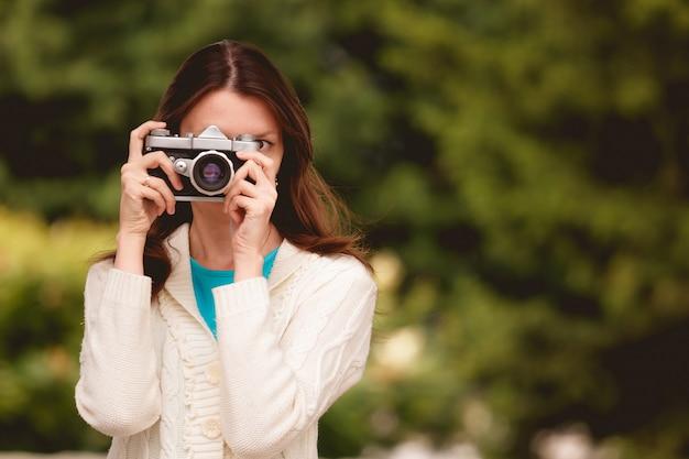 Hübsche brunettefrau, die ein foto in einem park macht