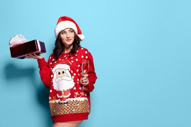 Hübsche brunettefrau im roten pullover mit sankt, glas champagner auf blauem hintergrund