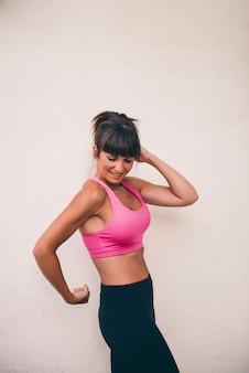 Hübsche brunettefrau wirft das unterrichten ihrer muskeln auf
