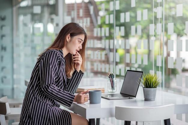 Hübsche, charmante asiatische geschäftsfrau, die mit einem laptop an einem modernen schreibtisch arbeitet