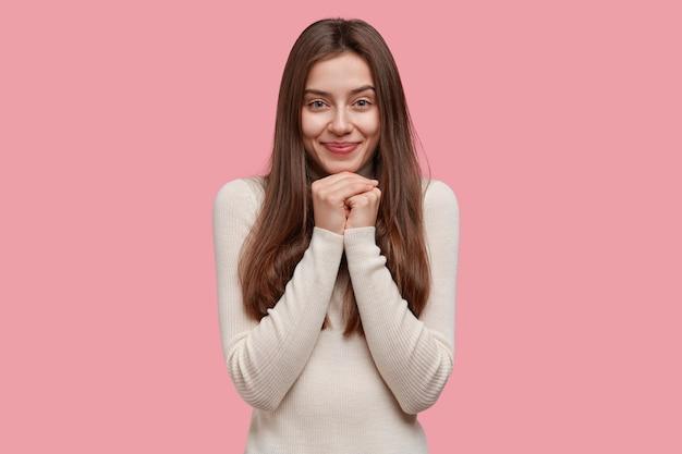 Hübsche charmante dame sieht mit glücklichen augen aus, hält die hände unter dem kinn und ist zufrieden, positive nachrichten zu hören