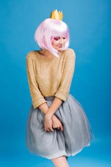 Hübsche charmante junge frau im grauen tüllrock, mit rosa haarschnitt. goldener pullover, krone auf dem kopf, schüchterne gefühle ausdrückend, mit geschlossenen augen lächelnd, party, feier.