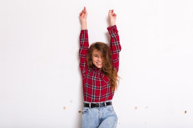 Hübsche charmante junge frau mit dem langen haar, das mit den händen oben aufwirft und lächelt, das rotes hemd auf weiß trägt