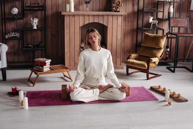 Hübsche dame beim yoga zu hause im lotussitz