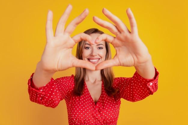 Hübsche dame bildete ein herz mit den händen, die das gesicht auf der gelben wand bedecken