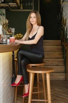 Hübsche dame, die an der bar sitzt und cocktail hat. wochenendbeschäftigung.