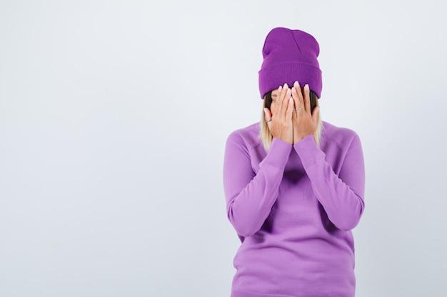 Hübsche dame, die das gesicht mit den händen in pullover, mütze bedeckt und deprimiert aussieht, vorderansicht.