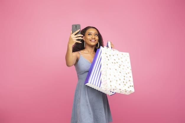 Hübsche dame, die ein selfie mit ihrem handy macht, während sie ein paar einkaufstüten hält