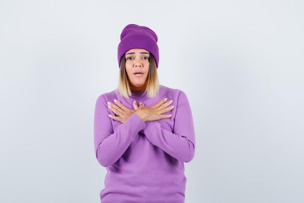 Hübsche dame, die gekreuzte hände auf der brust in pullover, mütze hält und verwirrt aussieht, vorderansicht.