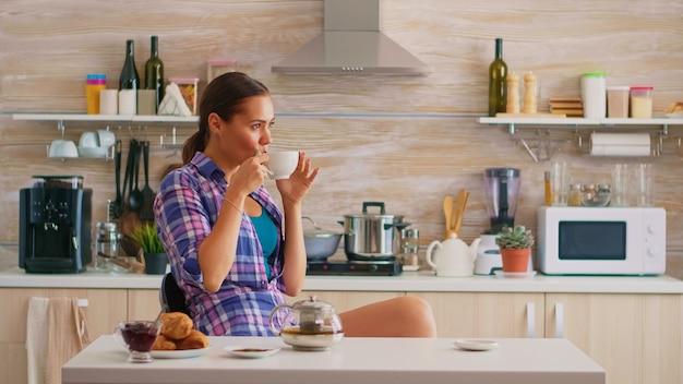 Hübsche dame, die grünen tee in der küche trinkt. junge frau, die morgens in der modernen küche in der nähe des tisches entspannt sitzt und leckeren natürlichen kräutertee aus weißer teetasse genießt