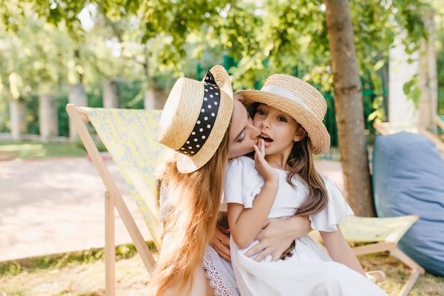 Hübsche dame, die in chaiselongue sitzt und tochter auf knien hält, guten sommertag genießend. außenporträt der schönen frau im weinlesehut, der kleines mädchen in der wange küsst.