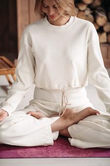 Hübsche dame, die mit geschlossenen augen auf lotussitz auf dem boden sitzt. gesundes und lifestyle-konzept