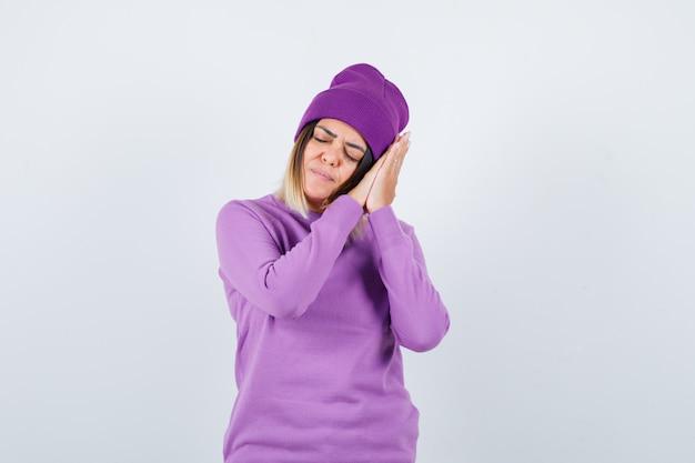 Hübsche dame, die sich auf palmen als kissen in pullover, mütze stützt und schläfrig aussieht, vorderansicht.