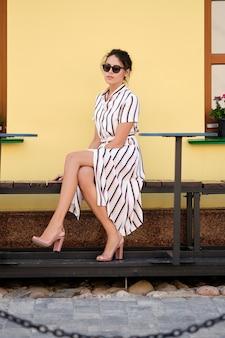 Hübsche dame im gestreiften kleid, das auf einer bank sitzt