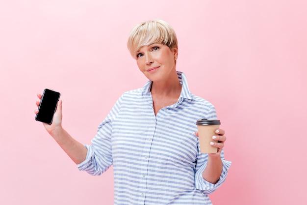 Hübsche dame im karierten outfit hält teetasse und smartphone