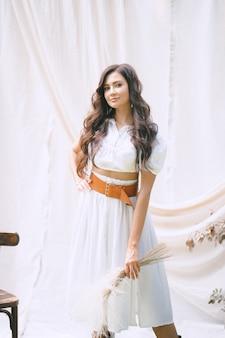 Hübsche dame im langen weißen kleid mit gürtel, der dekoration hält und im garten mit weißer wand während des tages schaut.