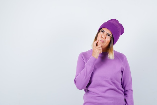 Hübsche dame im pullover, mütze, die den finger auf die wange hält, aufschaut und nachdenklich aussieht, vorderansicht.