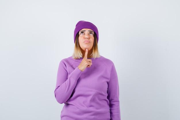Hübsche dame im pullover, mütze, die den finger unter dem kinn hält, nach oben schaut und düster aussieht, vorderansicht.