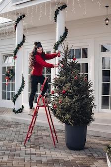 Hübsche dame im roten pullover, die auf trittleiter steht, während weihnachtsbaum im hof schmückt
