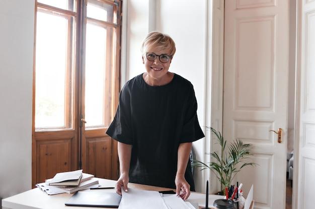 Hübsche dame im schwarzen outfit arbeitet mit dokumenten