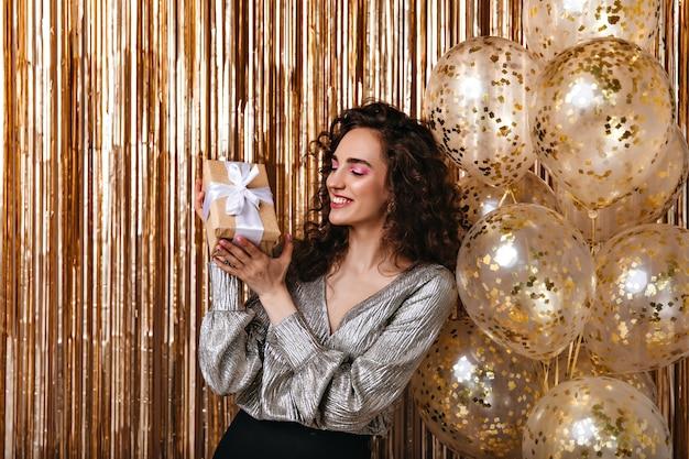 Hübsche dame in der guten laune, die geschenkbox auf goldenem hintergrund hält