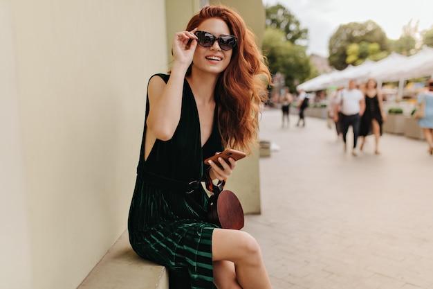 Hübsche dame in der sonnenbrille, die smartphone hält