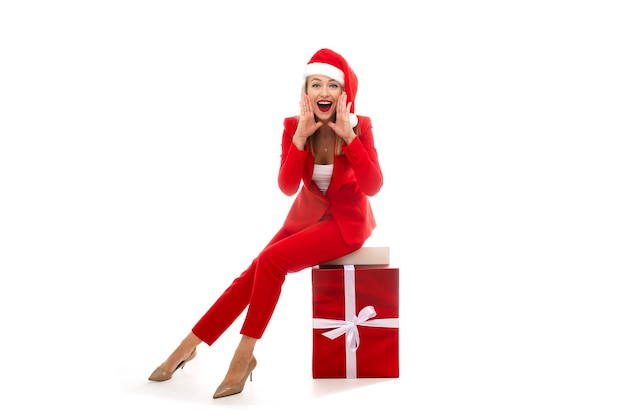 Hübsche dame in der weihnachtsmütze und im ausgefallenen roten kostüm, das auf eingewickelter geschenkbox sitzt und hohlen hände um ihren mund legt. urlaubskonzept