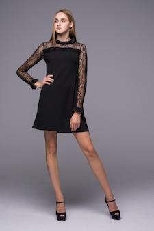 Hübsche dame in kurzem schwarzen kleid und hohen absätzen posiert