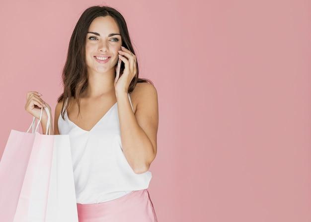 Hübsche dame mit einkaufsnetzen sprechend auf smartphone