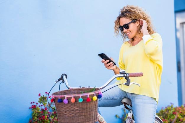 Hübsche dame mit gelbem pullover schaut lächelnd auf das telefon - freizeitaktivität im freien mit mobilfunkverbindung und trendigem fahrrad - aktive lässige weibliche leute im freien