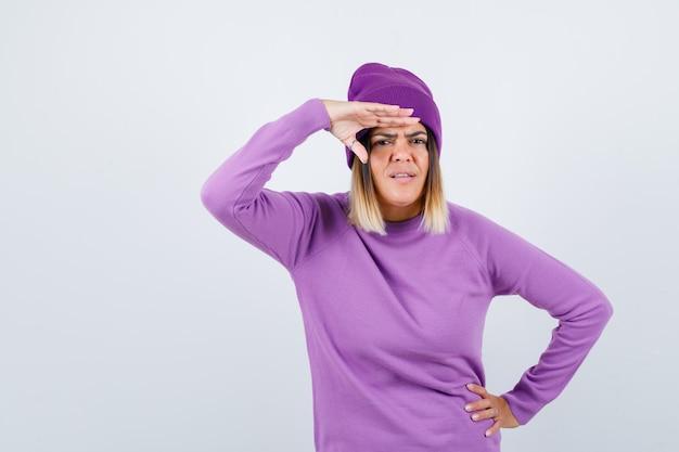 Hübsche dame mit hand über dem kopf in pullover, mütze und verwirrt, vorderansicht.