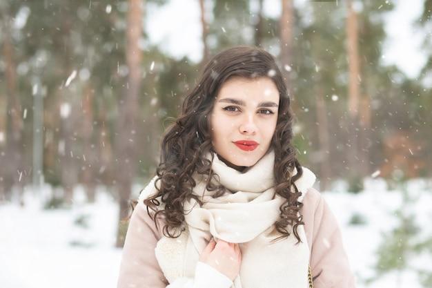 Hübsche dame mit langen haaren, die bei schneewetter im wald spazieren geht