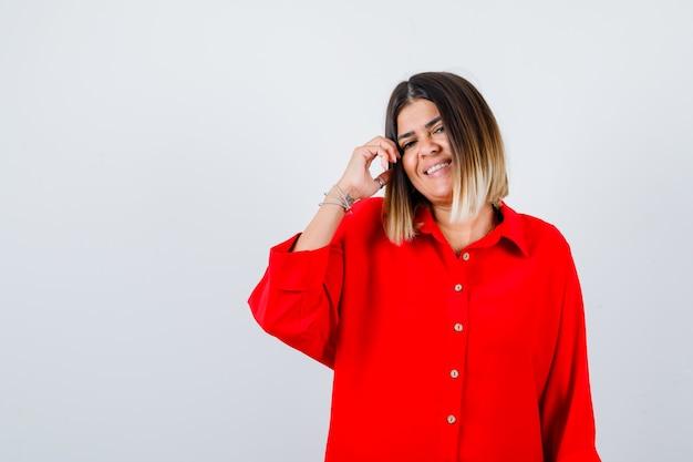 Hübsche dame posiert beim berühren der haare in roter bluse und sieht fröhlich aus, vorderansicht.