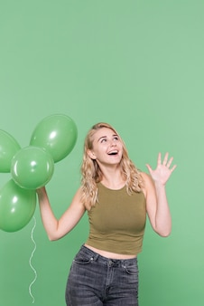 Hübsche damenmode, die mit ballonen aufwirft
