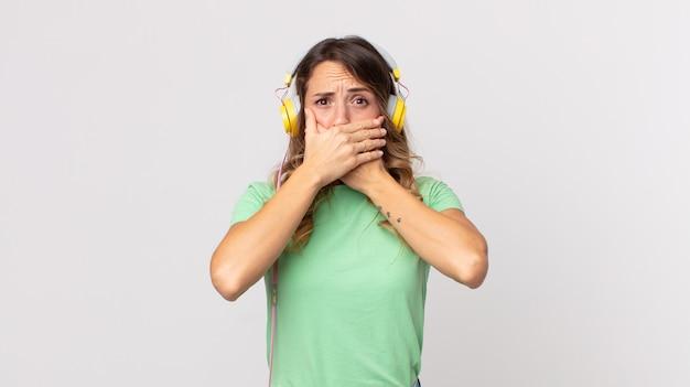 Hübsche dünne frau, die den mund mit den händen bedeckt, mit einer schockierten musik mit kopfhörern