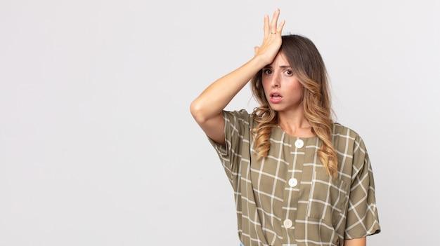 Hübsche dünne frau, die die handfläche zur stirn hebt und denkt, ups, nachdem sie einen dummen fehler gemacht oder sich daran erinnert hat, sich dumm zu fühlen