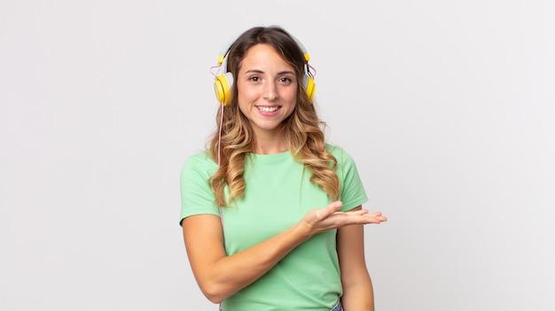 Hübsche dünne frau, die fröhlich lächelt, sich glücklich fühlt und ein konzept zeigt, das musik mit kopfhörern hört