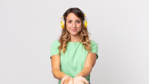 Hübsche dünne frau, die glücklich mit freundlichem lächeln lächelt und ein konzept anbietet und zeigt, das musik mit kopfhörern hört?