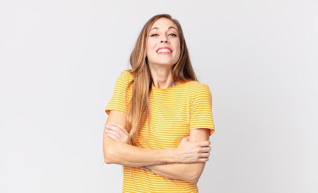 Hübsche dünne frau, die glücklich mit verschränkten armen lacht, mit einer entspannten, positiven und zufriedenen pose