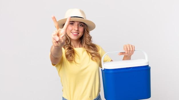 Hübsche dünne frau, die lächelt und freundlich aussieht, die nummer zwei zeigt und einen sommer-picknick-kühlschrank hält