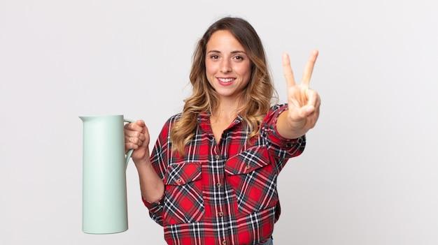 Hübsche dünne frau, die lächelt und freundlich aussieht, nummer zwei zeigt und eine kaffeethermos hält