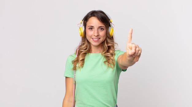 Hübsche dünne frau, die lächelt und freundlich aussieht und die nummer eins zeigt, die musik mit kopfhörern hört