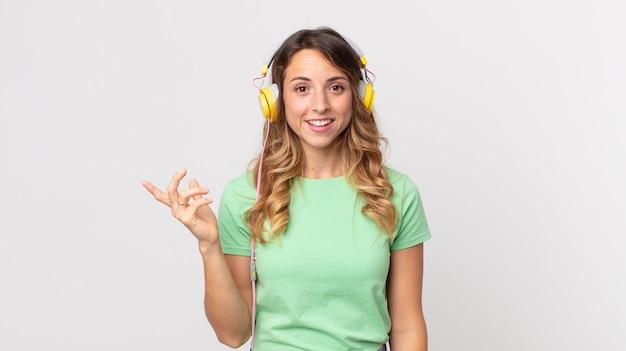 Hübsche dünne frau, die sich glücklich fühlt, überrascht, eine lösung oder idee zu realisieren, musik mit kopfhörern zu hören