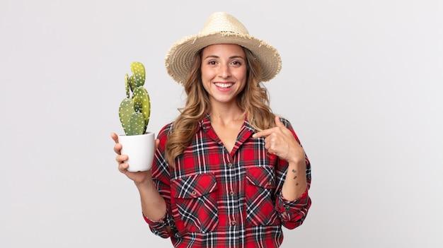 Hübsche dünne frau, die sich glücklich fühlt und mit einem aufgeregten halten eines kaktus auf sich selbst zeigt. bauernkonzept