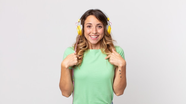 Hübsche dünne frau, die sich glücklich fühlt und mit einer aufgeregten musik mit kopfhörern auf sich selbst zeigt