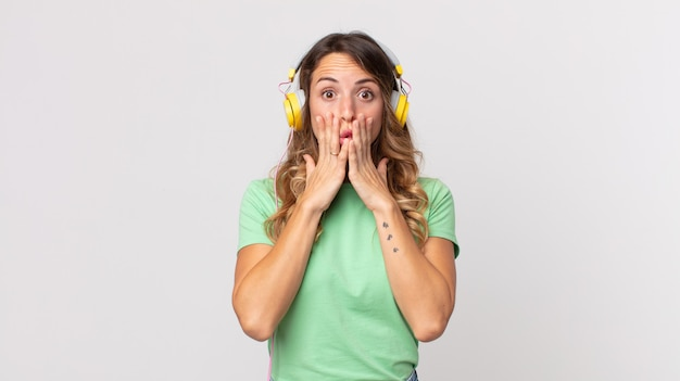 Hübsche dünne frau, die sich schockiert und verängstigt fühlt, wenn sie musik mit kopfhörern hört