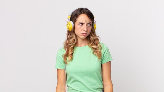 Hübsche dünne frau, die traurig, verärgert oder wütend ist und zur seite schaut und musik mit kopfhörern hört